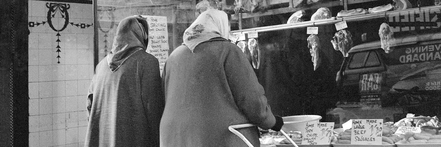 Black and white photo of two older women with headscarves on, one with a shopping trolly, standing outside what was then a butchers' window and is now the Young Vic box office entrance.
