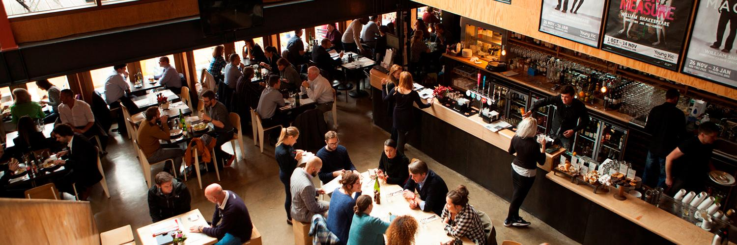 A busy photo of the The Cut Bar in the daytime with people seated at tables and waiting at the bar