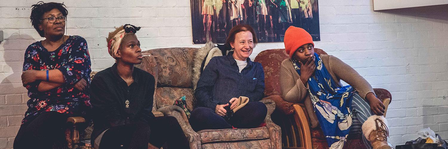 Four female participants of Taking Part Community Show Go Between sit on a sofa watching another group rehearse a scene. A range of expressions can be seen across their faces from laughter and smile to stern concentration.