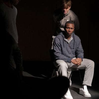 One of the young male performers sits on a chair bathed in light, looking across the stage as another man walks into the light from behind him, taunting him © Leon Puplett