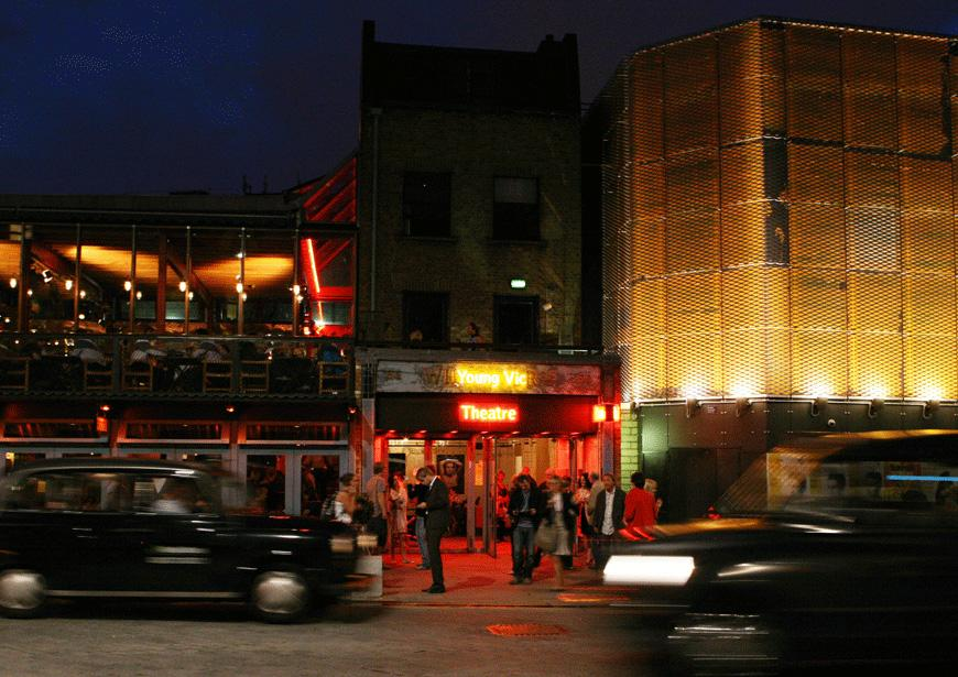 Photo of the exterior of the Young Vic building at night with people going in and out of the building and cars passing on The Cut
