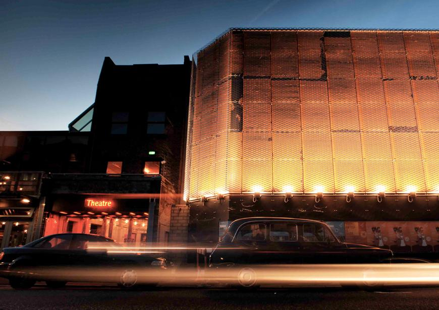 Long exposure photo of car passing the Young Vic box office and Main House at dusk with the light trail from the headlights clearly visible.