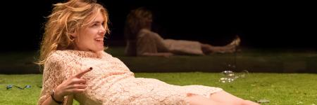 Billie Piper lying on a stage of grass in Yerma. Photo by Johan Persson.